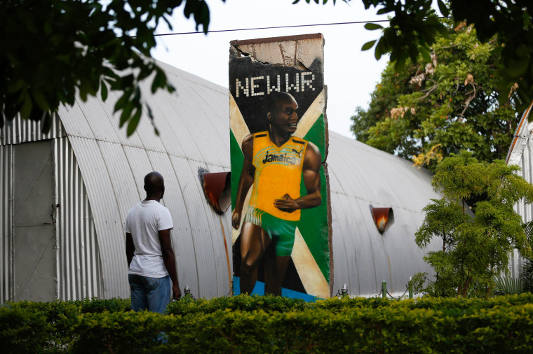 Image: A visitor looks at a section of the Berlin Wall painted with a mural of Jamaica's Olympic champion Usain Bolt in Kingston