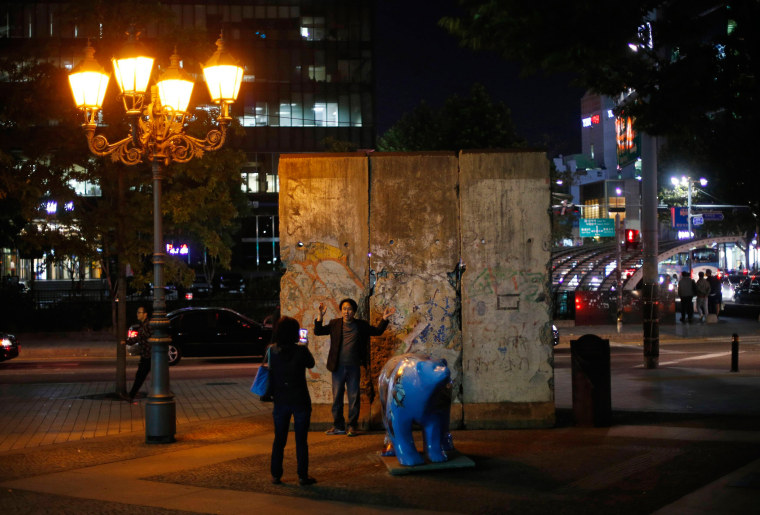 Image: A woman takes a photograph of her husband in front of part of the Berlin Wall at Berlin square in Seoul