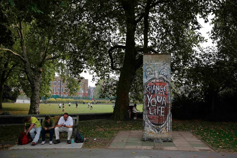 Image: Men sit on a bench next to a section of the Berlin Wall outside the Imperial War Museum in London