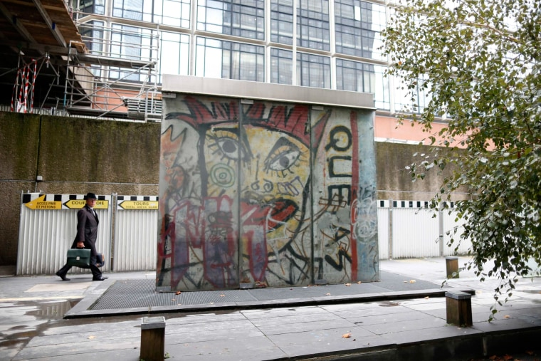 Image: A man walks near a piece of the Berlin Wall in La Defense business district in Courbevoie