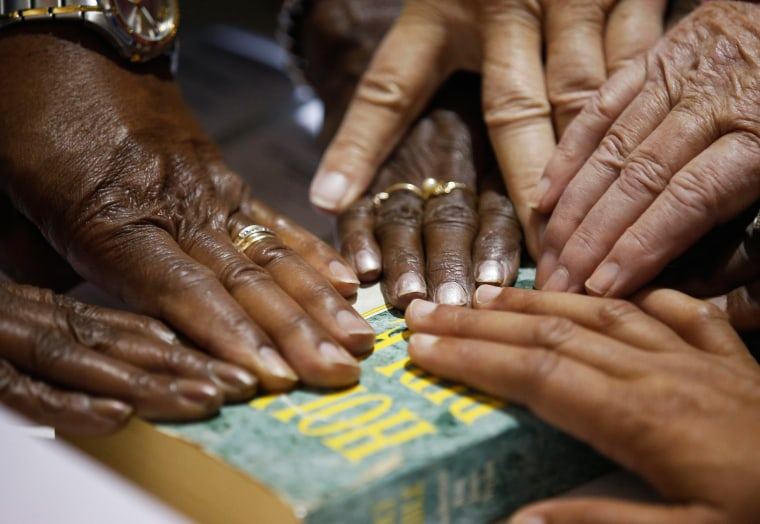 Image: Hands of poll workers are seen on a Bible as head precinct judge Deloris Reid-Smith reads the voters oath to poll workers before opening the polls at the Grove Presbyterian Church in Charlotte