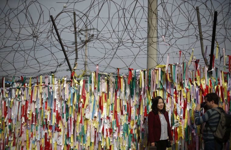 Image: A barbed wire fence decorated with South Korean national flags is pictured near the demilitarized zone