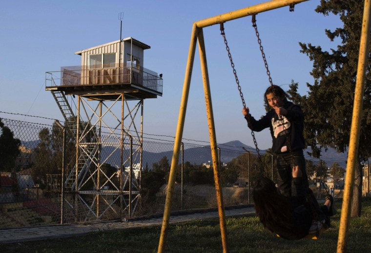 Image: File photo of children playing in a park next to a fence marking the United Nations buffer zone in a partially restricted area in the Turkish Cypriot controlled area of central Nicosia
