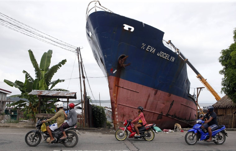 Image: Residents ride their motorcycles past a ship which ran aground during last year's Typhoon Haiyan in Tacloban city in central Philippines