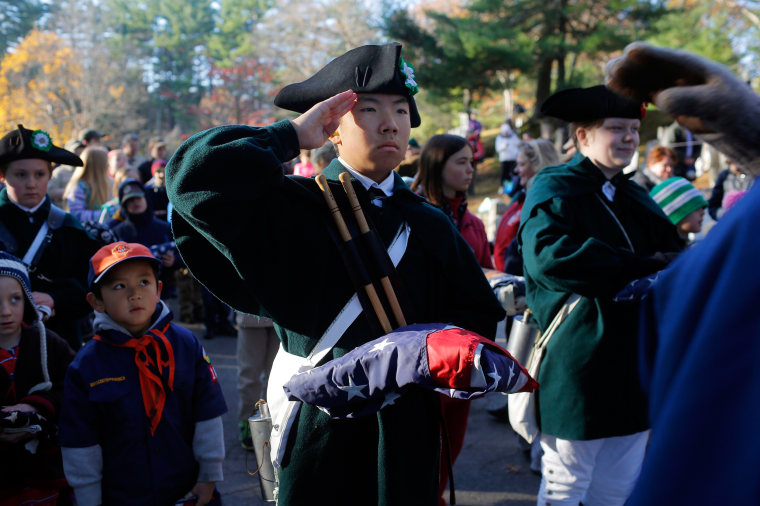 Image: A member of the Middlesex County 4-H Fife and Drum Corps presents a U.S. Flag for retirement during Veterans Day ceremonies in Concord