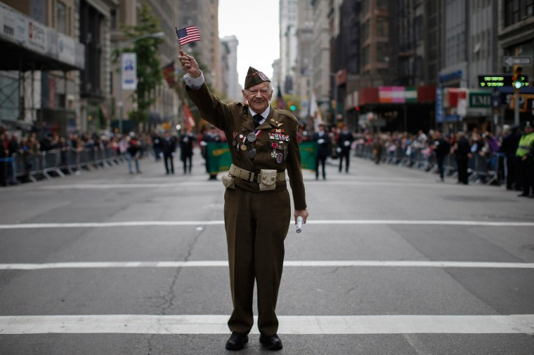 Image: United States Army World War Two veteran Frederick Carrier waves a flag during the Veterans Day parade in New York
