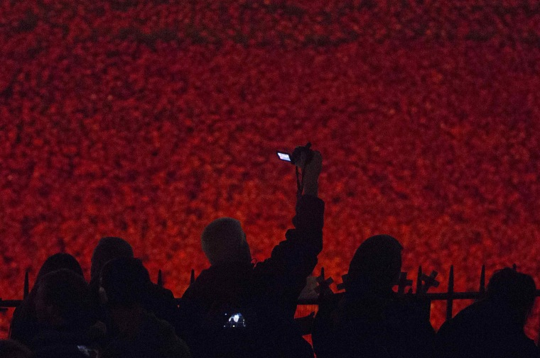 "Image: Visitors photograph the ""'Blood Swept Lands and Seas of Red"" as the art installation is illuminated at the Tower of London"