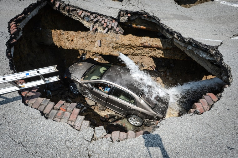 Image: A car at the bottom of a sink hole caused by a broken water line in Toledo, Ohio.
