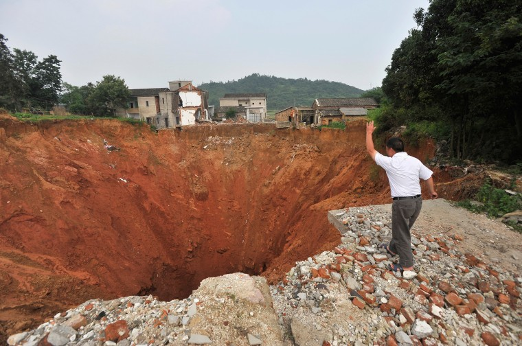 Image: A local resident throws a stone into a sinkhole near Qingquan primary school in Dachegnqiao town of Ningxiang