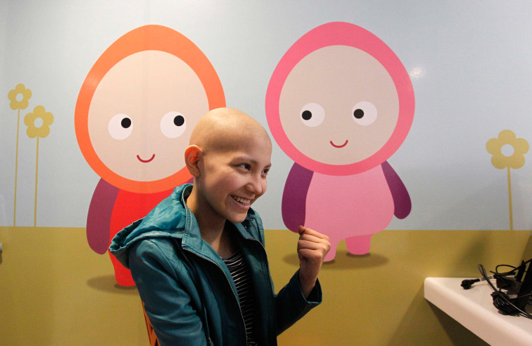 Image: Isidora Serrano, 14, who lost her hair due to chemotherapy to treat her bone cancer, reacts upon hearing from her doctor the positive results of a blood test during her daily treatment l in Santiago