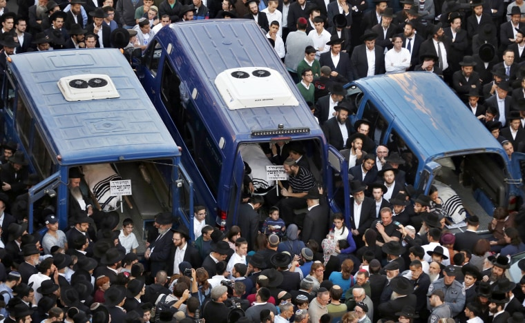 Image: The bodies of Kopinsky, Levine and Goldberg lie in vehicles during their funeral near the scene of an attack at a Jerusalem synagogue