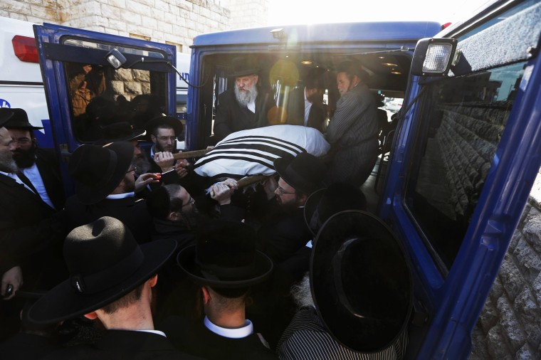 Image: Israeli Ultra-Orthodox Jews carry the body of Rabbi Mosheh Twersky onto a vehicle during his funeral in Jerusalem