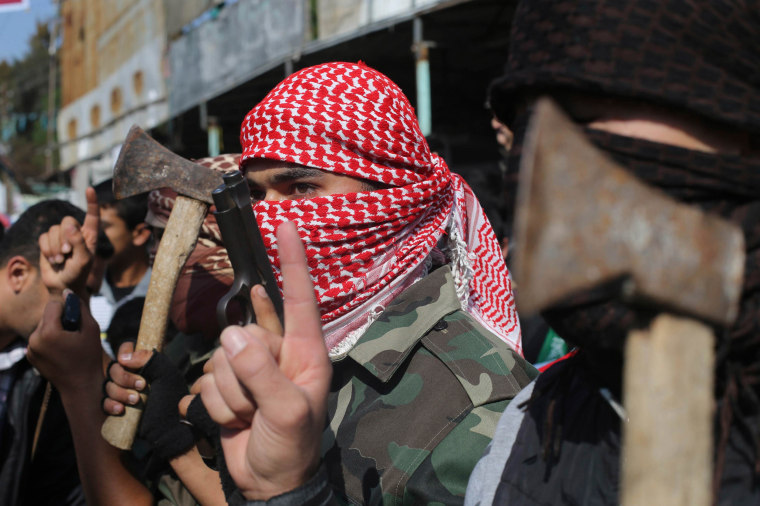 Image: Masked Palestinians hold axes and a gun as they celebrate with others an attack on a Jerusalem synagogue, in Rafah in the southern Gaza Strip