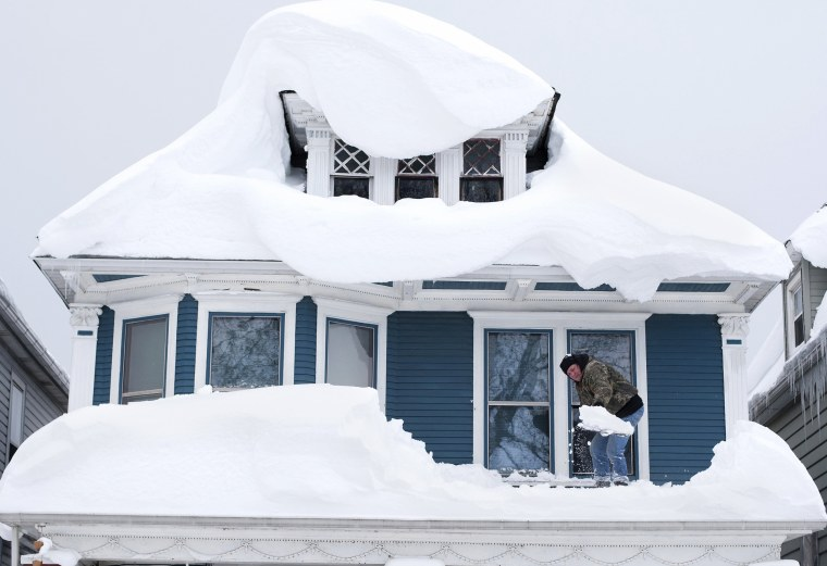 Image: Tom Wilczak shovels snow from the roof of his home following a storm in Buffalo