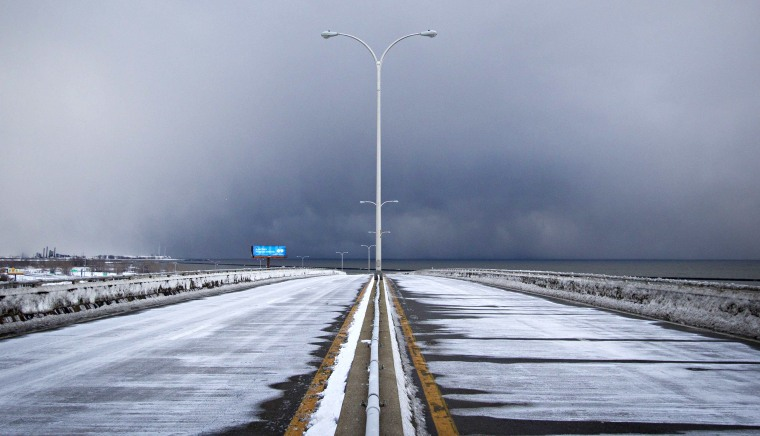 Image: Storm clouds and snow blow from Lake Erie over the still-closed Route 5 highway in Lackawanna, near Buffalo