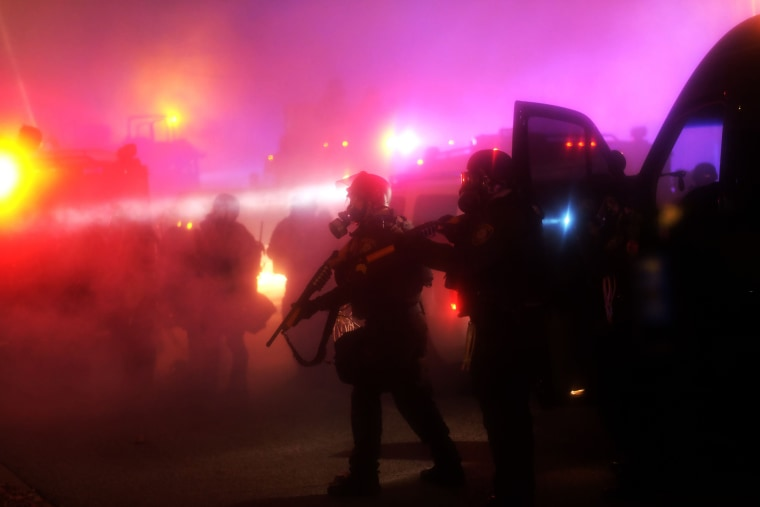 Image: Police are engulfed in tear gas during clashes with protesters