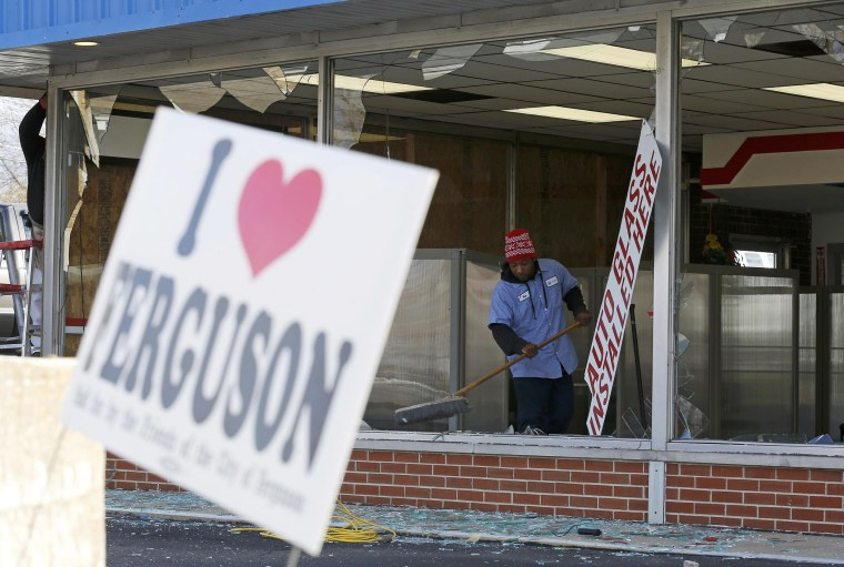 Image: People clean up a business that was damaged in riots the previous night in Ferguson