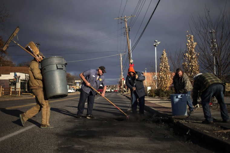 Image: Volunteers and workers clear soot from the site where a police vehicle was set ablaze in Ferguson