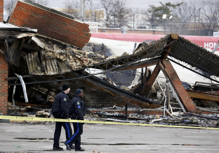 Image: Police officers look over the site of a building that was burned in riots the previous night in Ferguson