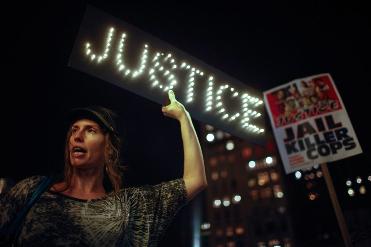 Image: Woman holds a sign as protesters rally in New York