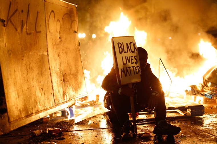 Image: Demonstrator sits in front of a street fire during a demonstration following the grand jury decision in the Ferguson, Missouri shooting of Michael Brown, in Oakland, California