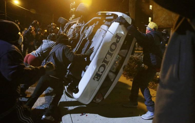 Image: Protesters flip over a Ferguson police car in Ferguson