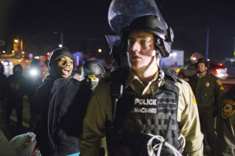 Image: A protester is detained by police officers during a second night of rioting in Ferguson