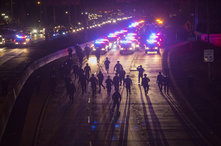 Image: California Highway Patrol officers walk to clear the 101 freeway from protesters in Los Angeles