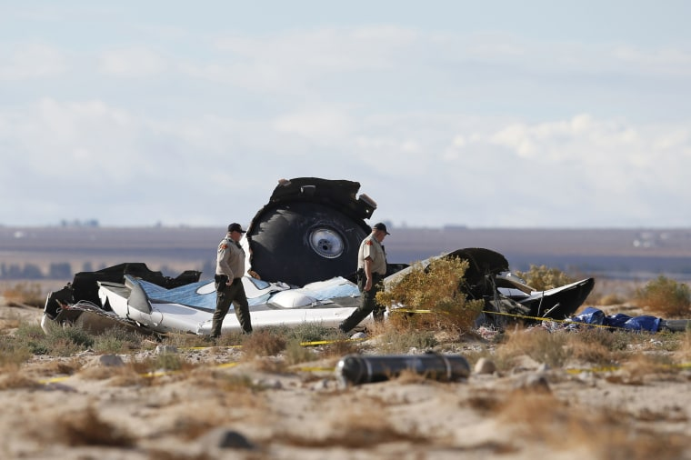 Image: Sheriff's deputies look at a piece of debris near the crash site of Virgin Galactic's SpaceShipTwo near Cantil