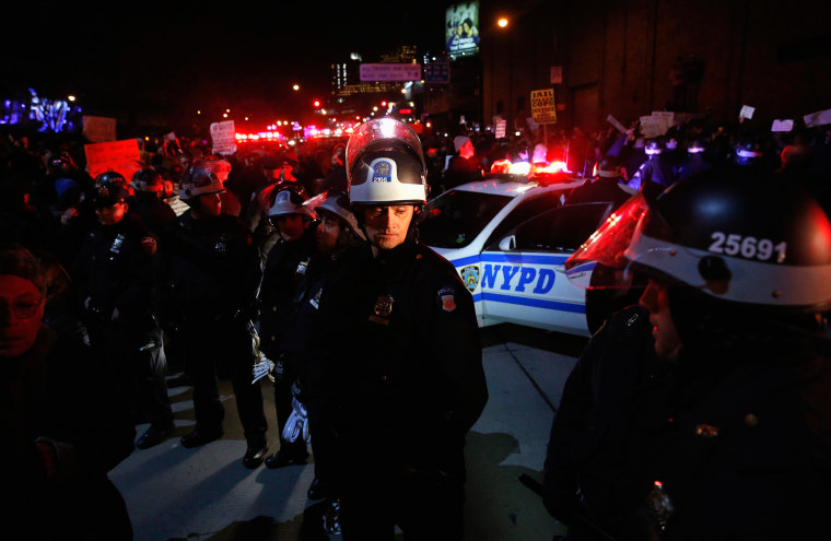 Image: NYPD police stand guard on the West Side Highway as protestors block traffic after the jury verdict in the death of Eric Garner, in New York