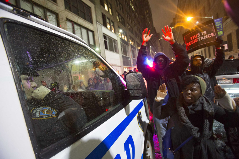 Image: A police officer watches protesters from her van during a march for chokehold death victim Eric Garner in New York