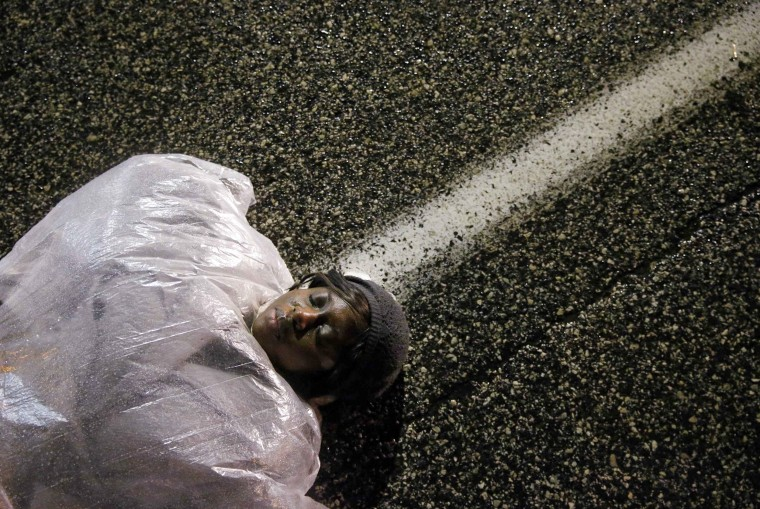 "Image: A demonstrator lays in the street during a ""die in"" protest against police violence in front of the Ferguson Police Department in Missouri"