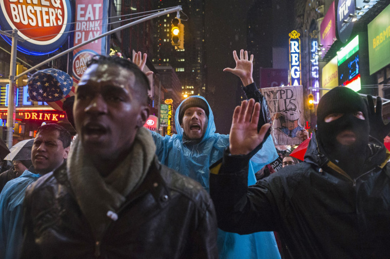 Image: Protesters, demanding justice for Eric Garner, hold up their hands while marching through Times Square, New York