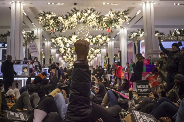 "Image: A protester, demanding justice for Eric Garner, raises his fist in solidarity with others after they stage a ""die-in"" at the Macy's department store in Herald Square, Manhattan, New York"