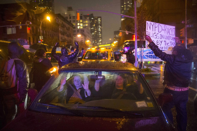 "Image: Women perform the ""Hands-Up Don't Shoot"" action in their car as protesters walk by during a march for chokehold death victim Eric Garner in New York"