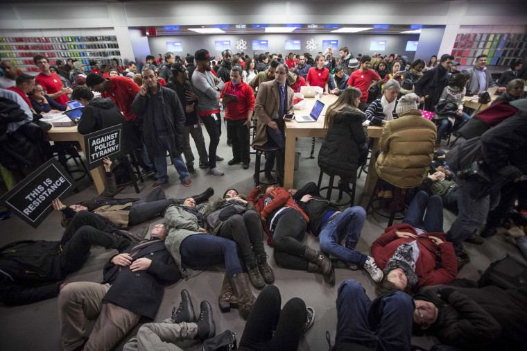 "Image: Protesters perform a ""Die-In"" in the Apple store on 5th Avenue during a march for chokehold death victim Eric Garner in New York"