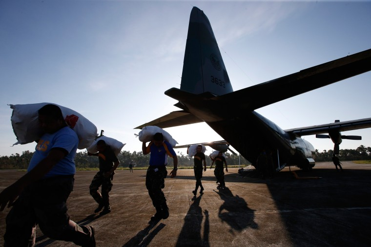 Image: Soldiers are silhouetted as they carry sacks containing relief goods for typhoon Hagupit victims in Borongan