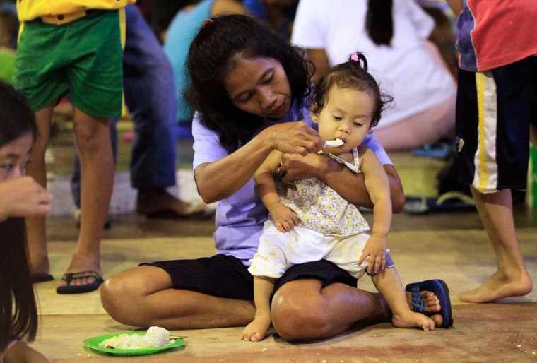 Image: A woman feeds daughter, as they join other residents taking refuge in gym which has been converted into evacuation center in San Juan town, Batangas