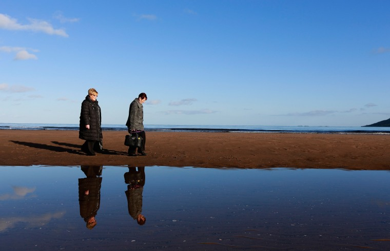 Image: Patricia Gearon and her sister Helen McKinley walk to the site where their brother Peter Wilson's remains were discovered at Waterfoot beach in County Antrim