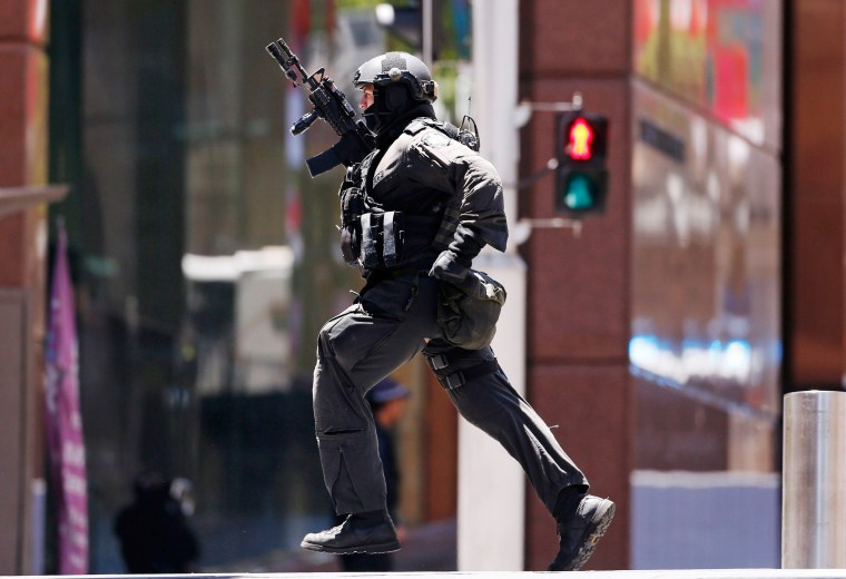 Image: A police officer runs across Martin Place near Lindt cafe, where hostages are being held, in Sydney