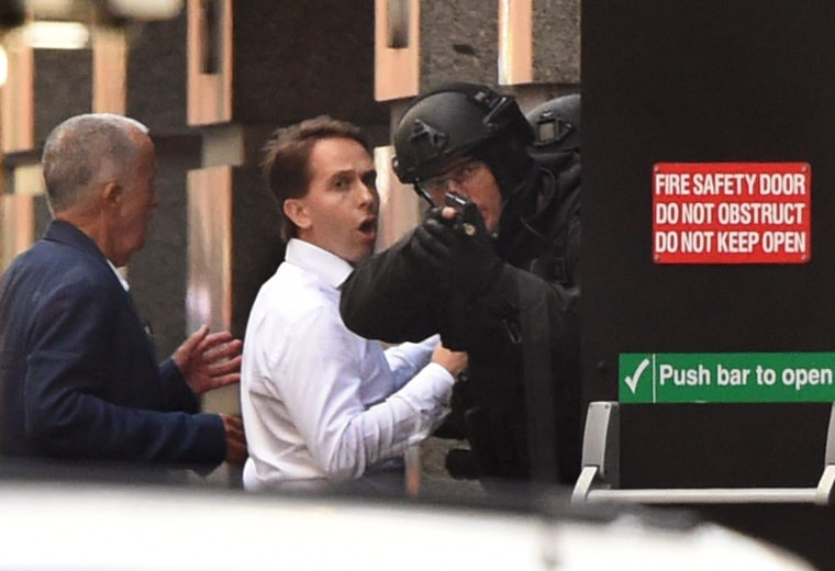 Image: Two hostages run for cover behind a policeman during a hostage siege in the central business district of Sydney