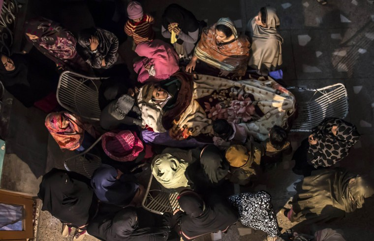 Image: Women mourn as they surround the body of their relative Osama Taher, a student who was killed during an attack by Taliban gunmen on the Army Public School, at his house in Peshawar