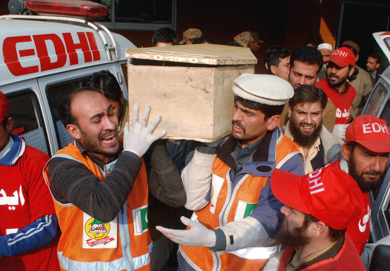Image: Rescue workers and family members carry the coffin of a student, who killed during an attack by Taliban gunmen on the Army Public School, in Peshawar