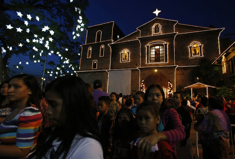 """Image: Devotees leave after attending the first of a nine-day pre-dawn mass, locally called """"Misa de Gallo"""", before Christmas at a church in Las Pinas, Metro Manila"""