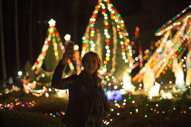 Image: A woman takes a selfie in front of the Balian Ice Cream House which is decorated for Christmas in Altadena