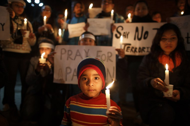 Image: A boy holding a candle attends a candle light vigil in Kathmandu