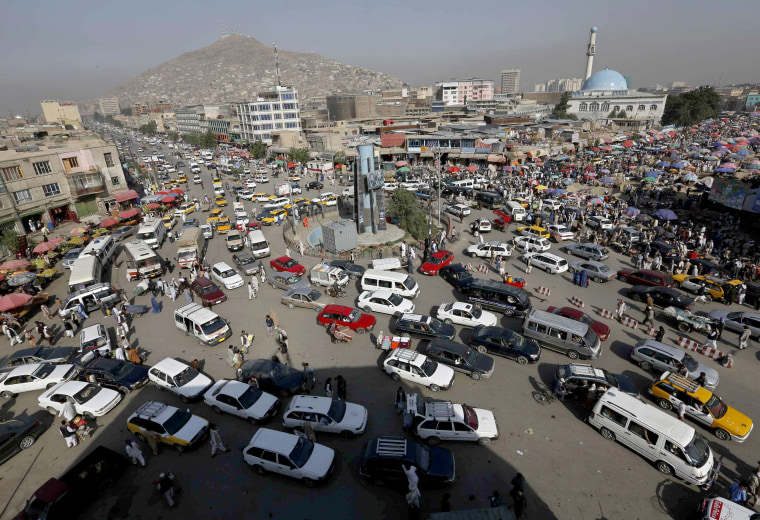 Image: Vehicles drive at a junction in downtown Kabul
