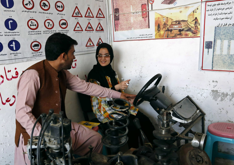 Image: Tahmina talks to her instructor during a practical lesson at a driving school in Kabul