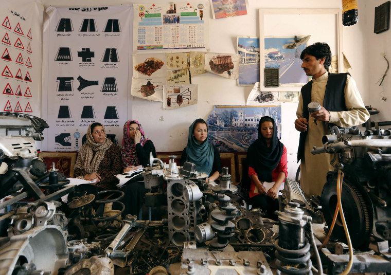 Image: An instructor teaches women about a car's mechanics during a technical lesson at a driving school in Kabul