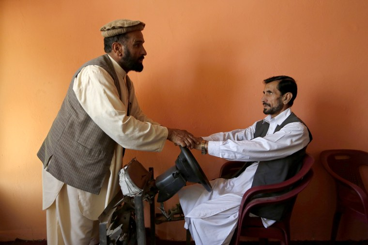 Image: An instructor teaches a man how to drive a car during a practical lesson at a driving school in Kabul